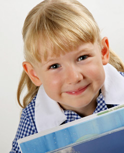 Girl in her school uniform, holding books.